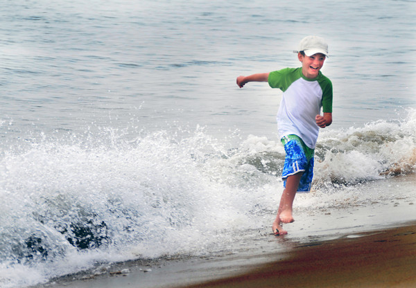 Salisbury: Morgan Souther, 8, gets runs from a wave on Salisbury Beach Sunday morning. Jim Vaiknora/Staff photo
