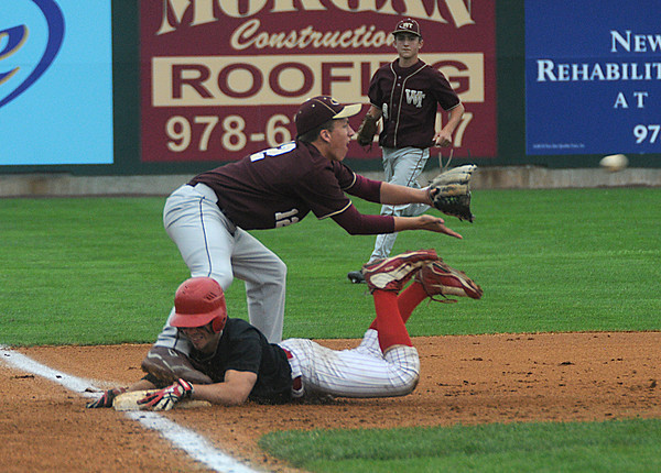 Lowell: Whittier 3rd basemen Andrew Wells waits for the throw as Amesbury's Chester Conant slides safetly into 3rd during the Wildcats 6-0 defeat of the Indians Saturday at LeLacheur Park in Lowell. Jim Vaiknoras/Staff photo