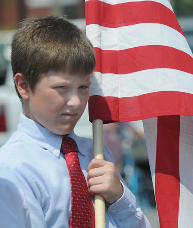 Newburyport: Thomas Isabel, a 7th grader at the Nock Middle School in Newburyport, carries the flag as he marches with his classmates in the Newburyport Memorial Day Parade Monday.  Jim Vaiknoras/Staff photo
