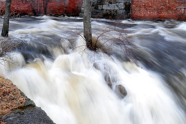 Amesbury: The Powow River roars through the upper millyard in Amesbury after the recent storms dumped rain in the area, and warm temperatures melted the local snow. Photo by Ben Laing/Staff Photo