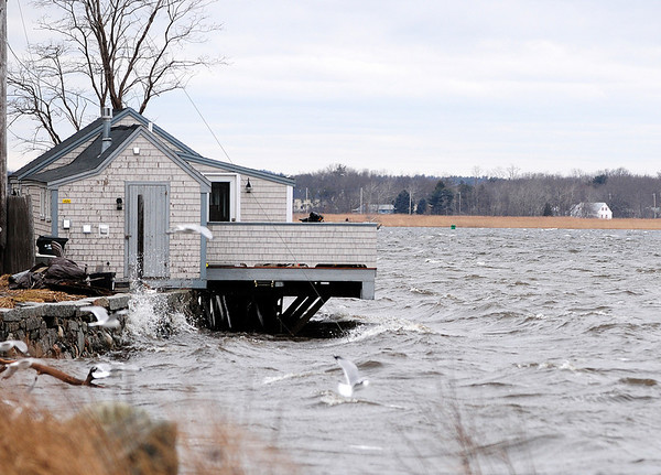 Newburyport: Waves lick the bottom of the porch at the clam shack on Water Street in Newburyport during Wednesday's high tide. Photo by Ben Laing/Staff Photo