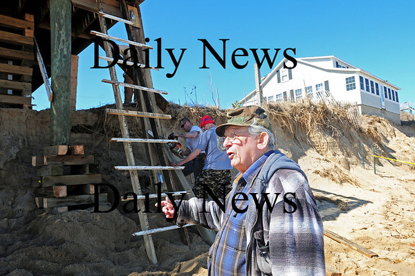 Newbury: Milton Tzitzenikos shows off the damage done to his home on Annapolis Way on Plum Island by the latest storm, as workers sure up the home's deck. Photo by Ben Laing/Staff Photo