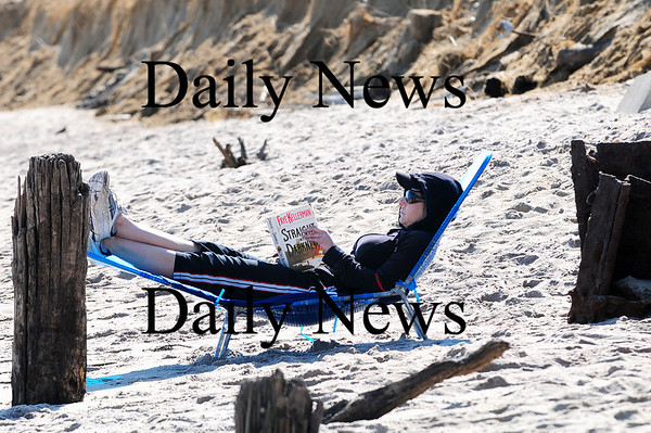 Salisbury: Tracey Bouchier of Lowell enjoys a good book and the warm temperatures at Salisbury beach Sunday afternoon. Photo by Ben Laing/Staff Photo
