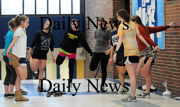 Byfield: Members of the Triton girls track team strech after practicing in the rain Monday afternoon. The girls track team is the two time defending CAL champions. Photo by Ben Laing/Staff Photo