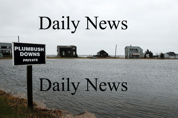 Newbury: The homes at Plumbush Downs along the Plum Island Turnpike are just out of reach of the rising water, as rain continues to fall along the saturated marsh. Photo by Ben Laing/Staff Photo
