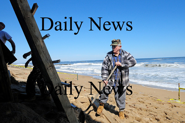 Newbury: Milton Tzitzenikos helps out as workers try to sure up the deck at Milton's Annapolis Way home on Plum Island. Photo by Ben Laing/Staff Photo