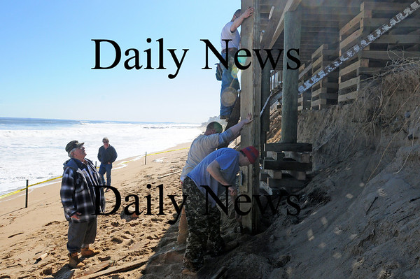 Newbury: Milton Tzitzenikos (left) watches as workers sure up the deck at his Annapolis Way home on Plum Island. The latest storm undercut the pylings and left the deck in danger of collapse. Photo by Ben Laing/Staff Photo