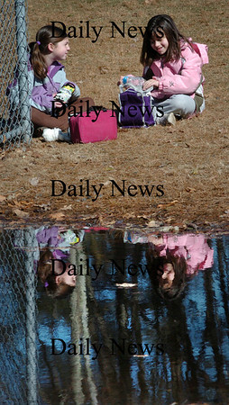 Salisbury: Emma Leahy, left, and Lindsey Gardella, both 9, are reflected in a wetland area at Salisbury Elementary School as they went out in the nice weather for snack time yesterday. Friday may be a different story as rain is expected in the region with up to four inches possible over the weekend raising the level of this big puddle. Bryan Eaton/Staff Photo