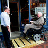 Newburyport: Loretta owner Ted Epstein holds the door for Tom Lyons as he rolls up a ramp the State Street, Newburyport has installed. Bryan Eaton/Staff Photo