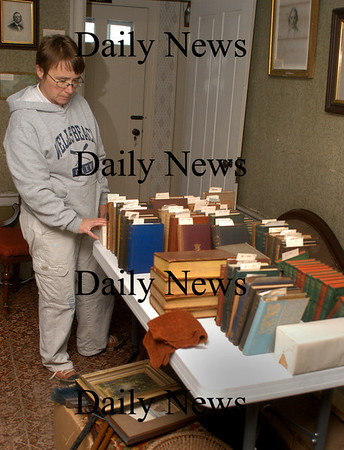 Amesbury: Janet O'Callahan, a friend of some members of the Whittier Home, checks out books slightly damaged in the museum. Recent heavy rain got access around a chimney requiring the removal of some books from the adjacent class case. Bryan Eaton/Staff Photo