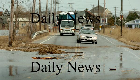 Newbury: Yesterday's high tide carried debris onto Plum Island Turnpike making only one lane of traffic passable. Bryan Eaton/Staff Photo