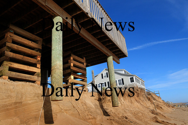 Newbury: All eyes were on 27 Annapolis Way during Monday's high tides, but the deck of number 29  was shored up from beneath as washed away sand left posts dangling. Bryan Eaton/Staff Photo