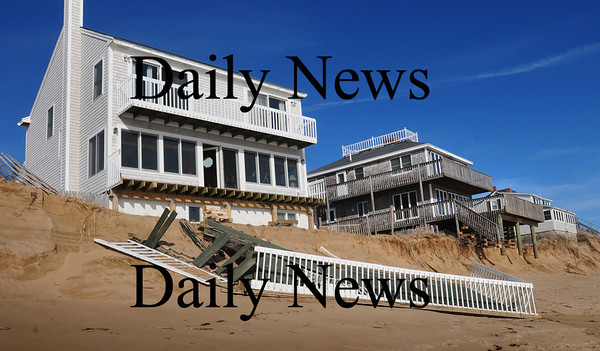 Newbury: The deck at 31 Annapolis Way on Plum Island was sawed off to protect the structure from the storm which could have damaged the whole building if it collapsed on its own. The middle home, number 29, has its deck shored up as the pilings hang over the beach. Bryan Eaton/Staff Photo