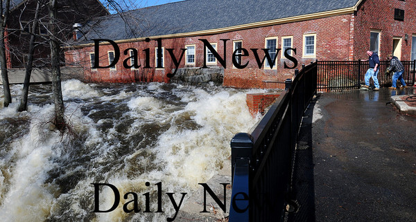Amesbury: Amesbury DPW workers install some sandbags along the Powow River in the Upper Millyard as some water was spilling over above the amphitheatre. Bryan Eaton/Staff Photo