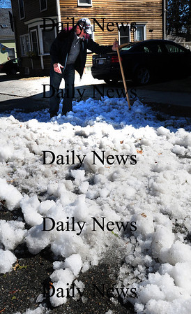 Newburyport: David Rafferty uses a little elbow grease and help from solar energy to break up a snowmound in front of his Oakland Street home in Newburyport late Saturday morning. Bryan Eaton/Staff Photo