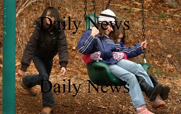 Amesbury: A little snow and drizzle didn't stop students from having a fun time at recess yesterday afternoon at the Cashman School in Amesbury. Tyda Thepbanthao, 8, takes a turn pushing her friends Rachel Bucher, 7, left, and Isabel Weatherbee, 8. Bryan Eaton/Staff Photo
