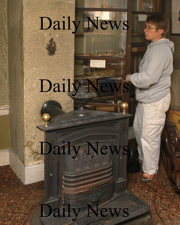 Amesbury: Janet O'Callahan, a friend of some members of the Whittier Home, checks out water damage in the museum. Recent heavy rain got access around this chimney requiring the removal of some adjacent books from the class case at right. Bryan Eaton/Staff Photo