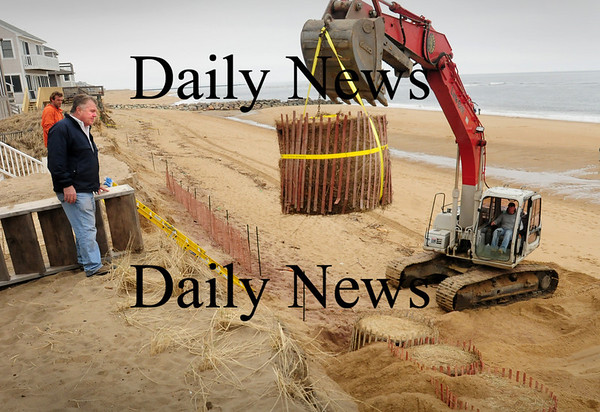 Newbury: Plum Island homeowner Bob Connors watches as one of several bales of hay wrapped in snow fencing is lowered into place on to the beach. Today's storm may create some street flooding, but Plum Island isn't to be battered as it was last weekend. Bryan Eaton/Staff Photo