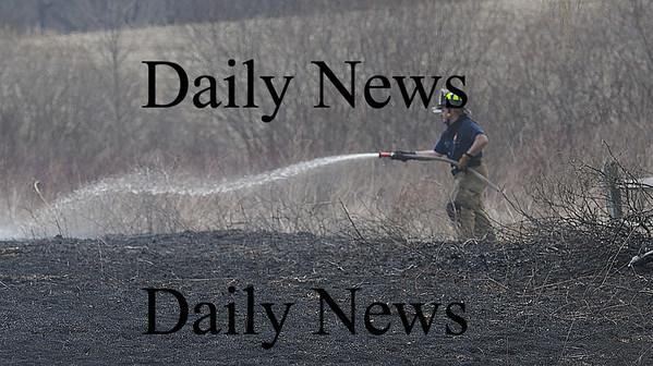 West Newbury: A firefighter hoses down a brush fire on Sullivan Court in West Newbury Sunday afternoon. Jim Vaiknoras/Staff photo