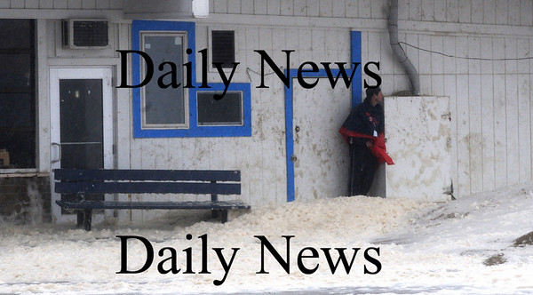Salisbury:A man braves he cold rain and wind as  surf and sea foam wash through Salisbury Beach Center Sunday morning. Jim Vaiknoras/Staff photo