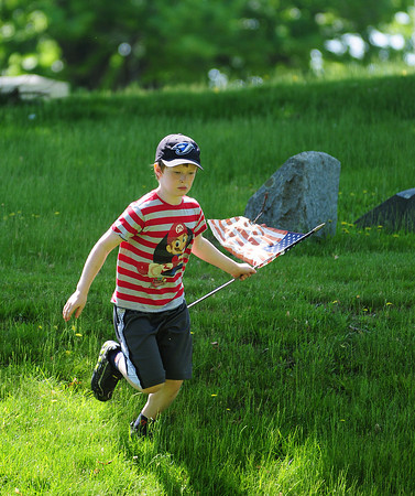 Amesbury: Owen Read, a second grader, races through the Veteran's Cemetery in Amesbury with an American flag Tuesday morning. Read and his classmates were replacing the flags in anticipation for Memorial Day next week. Photo by Ben Laing/Staff Photo