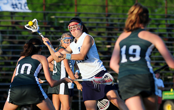 Byfield: Triton's Erin Curley (35) gets off a shot in a crowd of Pentucket players during Monday night's lacrosse game in Byfield. Photo by Ben Laing/Staff Photo