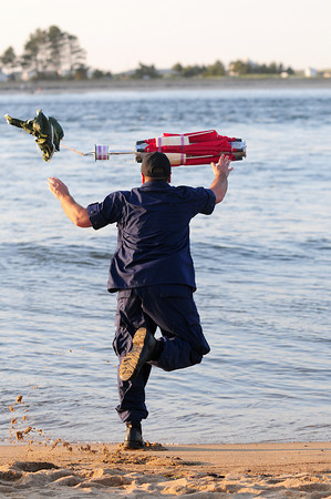 Newburyport: A Coast Guardsman tosses a marking buoy into the waters near the site of a missing swimmer on Plum Island point Tuesday afternoon. Photo by Ben Laing/Staff Photo
