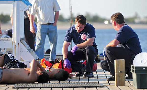 Newburyport: EMT's speak with two swimmers who were pulled from the waters at Plum Island point Tuesday afternoon. They were among seven rescued by private boaters before emergency personel arrived on scene. Photo by Ben Laing/Staff Photo