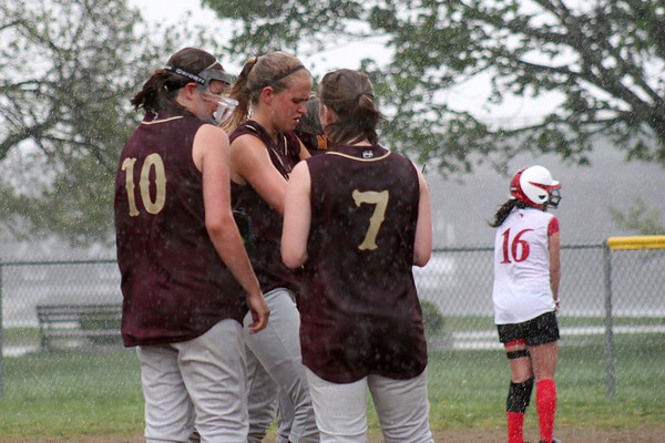 Newburyport: The Clippers softball players huddle together on the mound as the skies opened up during the start of Monday afternoons game against Masco. Photo by Ben Laing/Staff Photo