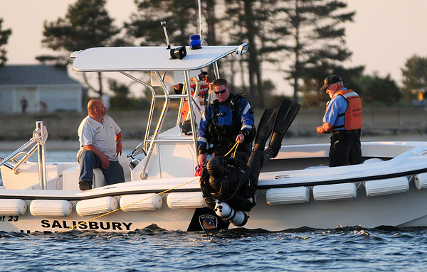 Newburyport: Members of the Newburyport Police Department's Dive Team plunge into the waters off of Plum Island point during a search for a missing swimmer Tuesday night. Photo by Ben Laing/Staff Photo