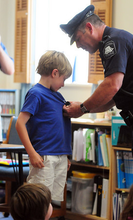 "Newburyport: Nicholas Petty is ""deputized"" by Newburyport police officer Chuck Vorderis at the Montessori School Tuesday afternoon. Nicholas and two of his classmates, Cian Magauran and Brendan Howland won the visit which included a ride in a police cruiser. Photo by Ben Laing/Staff Photo"
