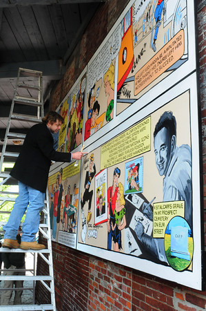 Amesbury: Artist Jon Mooers paints in the borders of a cartoon-mural of Al Capp's biography just before a small ceremony Saturday at the Hamilton Gateway entrance to Amesbury's Upper Millyard. Bryan Eaton/Staff Photo