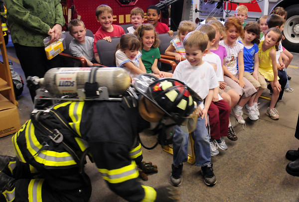 Rowley: Pine Grove kindergartners get a laugh as Rowley firefighter David  Carpentier crawls around on the floor teaching them the safe way to try to get out of a home if it's on fire as heat and toxic smoke rises. The kindergartners also got a tour of the fire engines after a talk on fire safety. Bryan Eaton/Staff Photo