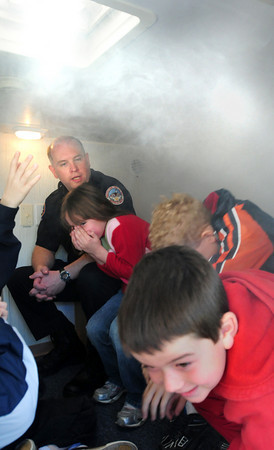 Newbury: Byfield firefighter Doug Janvrin talks to first-graders as they react to smoke filling a room in the Student Awareness of Fire Education (SAFE) House, on loan from the Amesbury FIre Department on Thursday morning. Newbury and Byfield firefighters brought the SAFE House, which teaches children about fire safety, to Newbury Elementary School. Bryan Eaton/Staff Photo