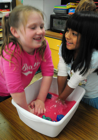"""Katie Gallagher, 6, left, and Anya Potvin, 5, squeeze spongy letters to clean them out in Linda Gershuny's kindergarten class at the Brown School in Newburyport on Monday afternoon. They used the letters to paint the """"chicka chica boom boom"""" t-shirts they created. Bryan Eaton/Staff Photo"""