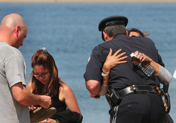 Newburyport: Newburyport Police Lt. Mark Murray, gets a hug from the mother of Marina Khon who was swept away on Plum Island Point on Tuesday. He and Lt.  Siemasko, left, had come to tell her and friends and family that the search had been called off. Bryan Eaton/Staff Photo