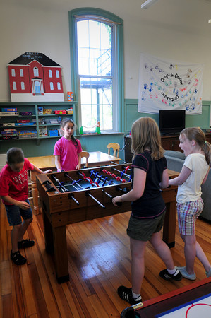 Newburyport: Adults and children not yet old enough to attend the Drop-in Center at the Kelley School, like those pictured playing foosball, got to tour the facility during the grand opening and ribbon cutting. Clockwise, from left, fourth-grader Ryan Snowdon, 8, of the Bresnahan School and Molin School fifth-graders Meredith Vartabedian, Emma Fisher, both 10, and Natalie Edwards, 9. Bryan Eaton/Staff Photo