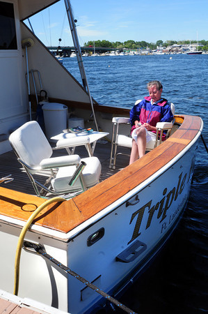 Newburyport: Sue Kilborn of South Hampton, N.H. texts her granddaughter aboard her boat Triple Play at the Newburyport waterfront. The boat is moored at Merri-Mar Yacht Basin usually, but was the waterfront awaiting a crew to repair some electronic components. Bryan Eaton/Staff Photo