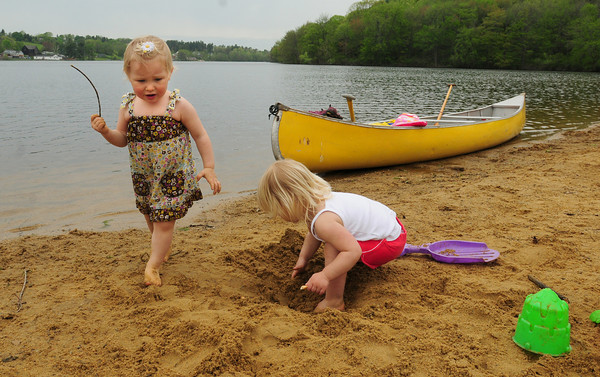 Amesbury: Clementine Teak, 2, looks for twigs as her friend Stella Becker, 2, starts a sand castle to put the twigs atop at Lake Gardner Beach yesterday morning. They paddled over in the unseasonablyl warm weather with their mothers, Heather Becker and Maya Teak, from their Whitehall Road homes. Bryan Eaton/Staff Photo