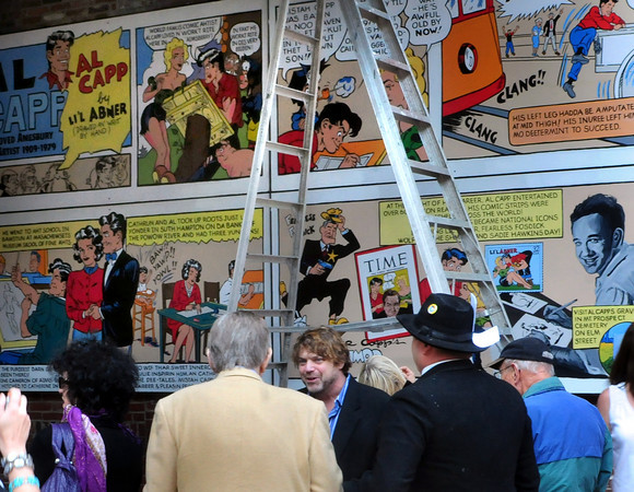 Amesbury:  Artist Jon Mooers talks to people in front of his cartoon-mural of Al Capp's biography just before a small ceremony Saturday at the Hamilton Gateway entrance to Amesbury's Upper Millyard. Bryan Eaton/Staff Photo