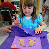"Salisbury: Madyson Hayes, 4, wraps a Mother's Day present with the help of preschool teacher Julie Deschenes at Salisbury Elementary School on Thursday morning. The children were read the book ""My Love For You Is"" and then created their copy of the book they illustrated. Bryan Eaton/Staff Photo"