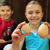 Groveland: Katie Klosowski, 8, holds a medium chicken egg, left, and another egg that weighed in at 4.1 ounces, that she plucked from her family's henhouse in Groveland. She collects the eggs, and her brother Andrew, 10, does the feeding. Bryan Eaton/Staff Photo