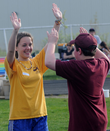 Newburyport: Alex Canning gets a high 5 from Michael Short during the Clipper jr practice  at Fuller field in Newburyport. The program has high school track athletes work special needs athlete on track and field skills. Jim vaiknoras/Staff photo