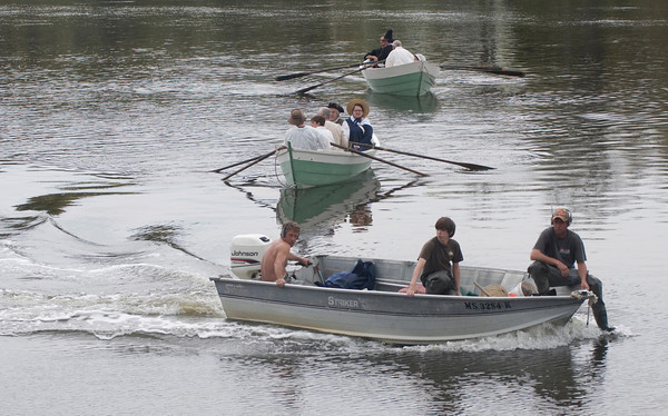 Newbury: A trio of clammers cuts across the bow of a group of reinactors Saturday who are making their way to near the point along the Parker River were the first settlers of Newbury landed in 1635. The landing was part of Newbury's 375th  celebration. Jim Vaiknoras/Staff photo