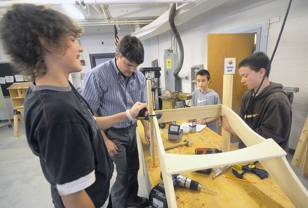 Amesbury: Patrick Scanlon, Chris Bruno, and Daniel Triano work with tech ed teacher Jim Firmes as they build an adirondack chair in shop during the Amesbury Middle School Celebration of Learning Open House Thursday night. The chairs are being raffled off to raise money for the Theraputic Horseback Riding program which provides riding to special needs kids in Amesbury. Anyone interested in buying a ticket can contact Cathy Mamakes at the Middle School. Jim Vaiknoras/Staff photo