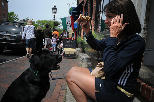 Newburyport: Molly patiently watches the every move of a muffin being eaten by Bonnie Hevsch on Liberty Street in Newburyport Saturday morning. Jim Vaiknoras/Staff photo