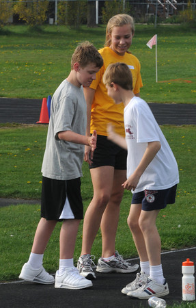 Newburyport: Zack Kelliher high fives Jake Kennefick with newburyport high school student  Haley Johnson during the Clipper jr practice  at Fuller field in Newburyport. The program has high school track athletes work special needs athlete on track and field skills. Jim vaiknoras/Staff photo