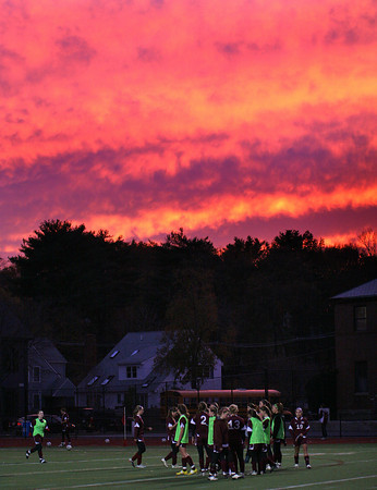 Newburyport: The Newburyport Girls Soccer team warms up before Wednesday night's game against Belmont beneath a firey sunset. Photo by Ben Laing/Staff Photo