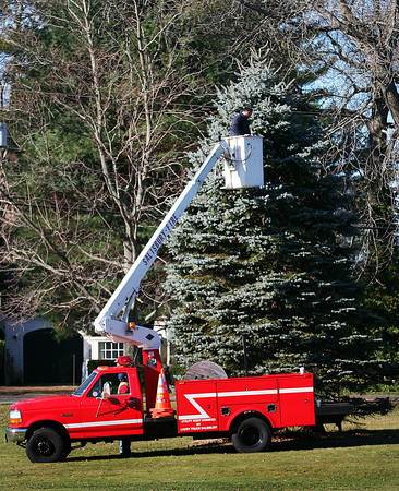 Newbury: Newbury firefighters string Christmas lights on a tree at the Upper Green Monday morning, as the area grears up for the holiday season. Photo by Ben Laing/Staff Photo