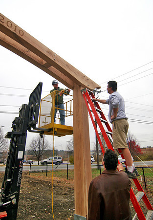 Newburyport: Mark Richey of Mark Richey Woodworking, drills a hole through a piece of oak with the help of Dave Jasneski and Ray Castagna. The trio were installing an archway over the entrance to the rail trail along Parker Street. Photo by Ben Laing/Staff Photo